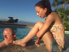 Foot fetish brunette in a miniskirt giving a foot job outdoors
