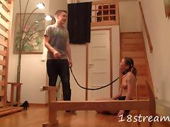 An obedient slave teen wears a collar while sucking cock