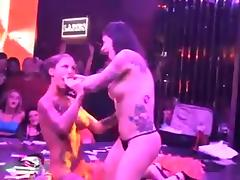 Two hot brunettes dancing around a pole in thong