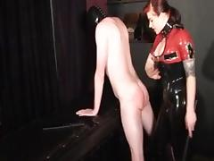 Redhead dominatrix in latex tortures her thrall