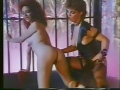 Brunette in leather spanks girlfriend and licks pussy in cage