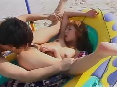 Japanese babe in a raft on the beach is happy to fuck her man