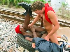 A white gay guy fucks a black guy next to the train tracks