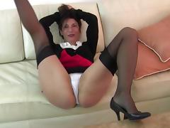 Horny housewife relaxes on the couch rubbing her hairy biscuit