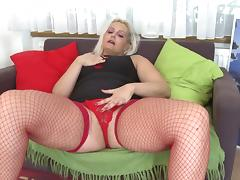 Blonde cougar in red stockings uses the glass dildo with pleasure