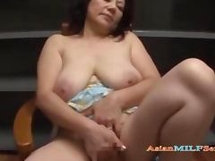 Busty Mature Woman Masturbating Using Vibrator While Sitting On The Chair