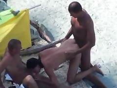 Slutty chick gets fucked by two men on a nude beach