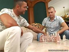Two gays play chess and bang doggy style on a sofa