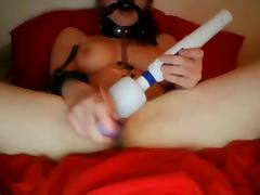 Masked, chains and clamps on girl playing on cam