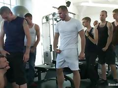 A tied up guy sucks huge dicks and get toyed in a gym