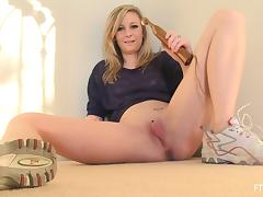 A blonde solo babe fingers and fists her pink pussy